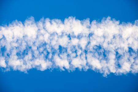 straight line: White clouds in a straight line on blue sky. Stock Photo