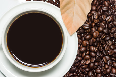 frijol: Negro caf� en la taza y granos de caf� tostado de fondo. Foto de archivo