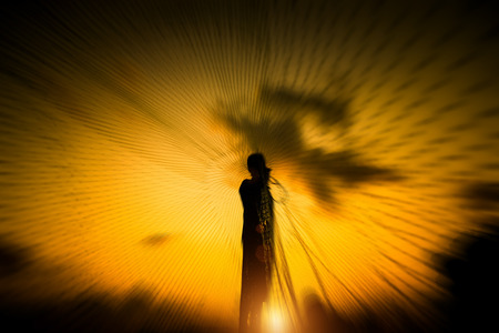 fish net: Silhouettes fisherman throwing fishing nets during sunset, Thailand.