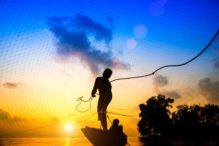 pescador: Siluetas pescador lanzando redes de pesca durante el atardecer, Tailandia. Foto de archivo