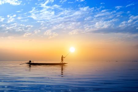 Bel cielo e sagome di pescatori minimo al lago, Thailandia.