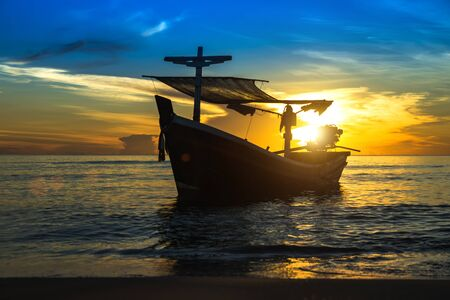 afloat: Silhouettes of Fishing boat on the beach. Stock Photo