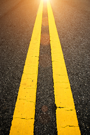 The yellow traffic lines on the road with sunlight.