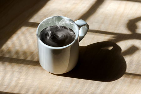 white coffee: Lighting from window with hot white coffee cup on the wooden. Stock Photo
