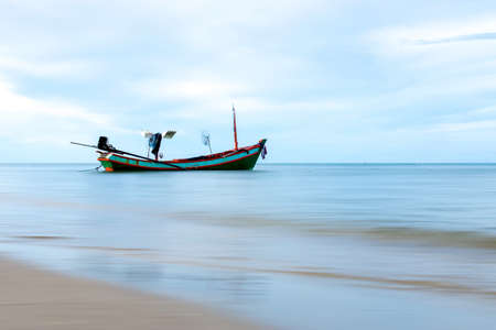 afloat: Fishing boat on the beach with blue sky and sand.
