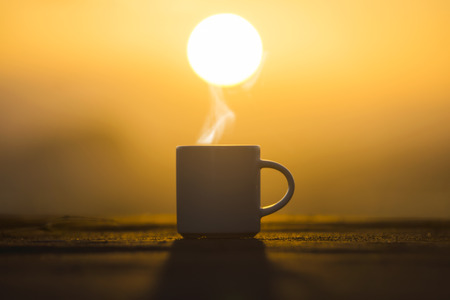 Silhouettes Coffee cup in the morning time with sunrise.