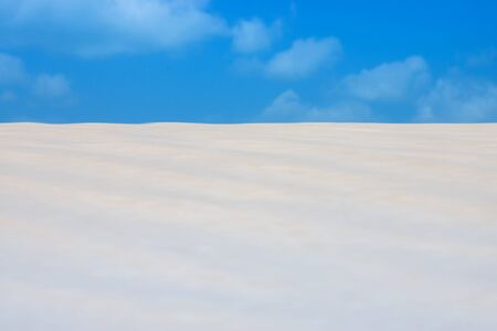 aridness: Sand and blue sky on the beach. out of focus image.