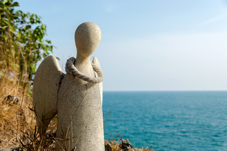 grave site: Guardian angel statue on the cliffs of the island, Thailand.