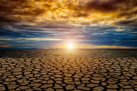 Cracked ground from Global warming with sunset and color cloud. Stock Photo