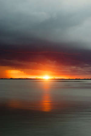 sotto la pioggia: cielo al tramonto sul lago sotto nuvola di pioggia.