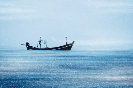 Fishing boat on the sea with snowfall with mist in winter color tone.