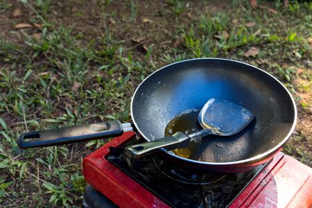 Portable gas stove and a frying pan after use in the camp.