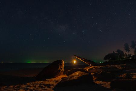 Lanterns on the beach in the dark night with star. Foto de archivo
