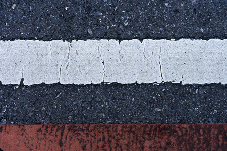 Old white and red traffic lines on the road. Stock Photo