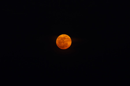The red full moon in the twilight hour.