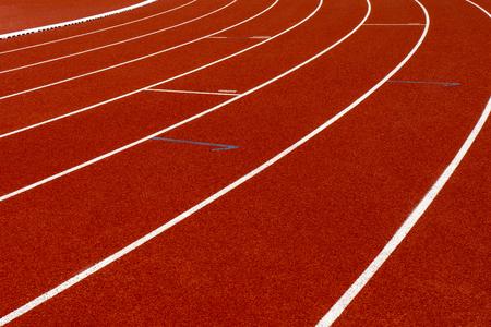 Cinta de correr roja con línea blanca en el estadio.