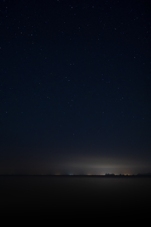 Vertical image of Stardust in the night with noise and grain on the blue sky with soft light of city in bottom.