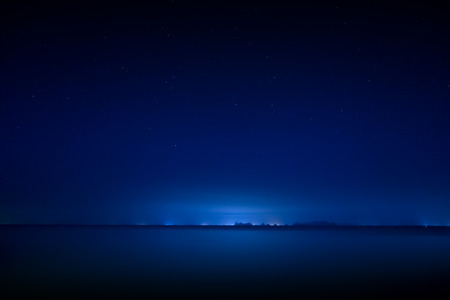 Stardust in the night with noise and grain on the blue sky with soft light of city in bottom.