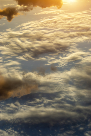 Vertical image of the clouds on sky with sunlight.