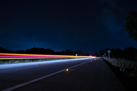 Motion light of the car on the road in the dark night with stars on the sky. 스톡 콘텐츠