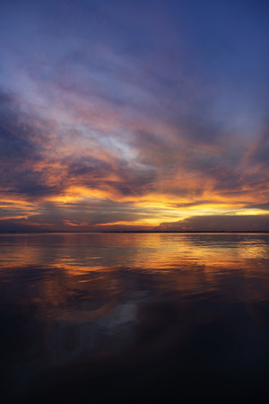 Vertical image of Twilight sky with multicolor cloud and water reflection on the lake.