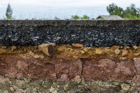 Die Schicht der Asphaltstraße mit Boden und Felsen. Unfokussiertes Bild.