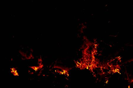 The sparkle of the flames in the dark background with black space. Stockfoto