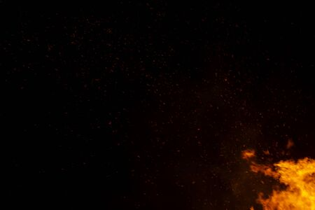 The floating light and sparkle of the fire in the dark background. Stockfoto