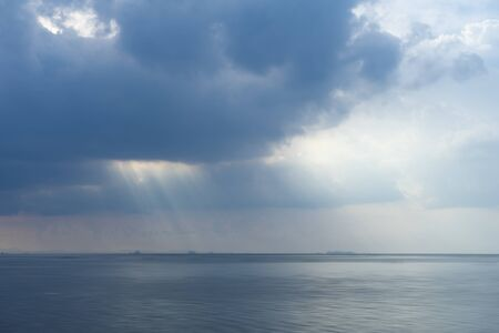 Soft image of the lake with sunlight under the clouds.