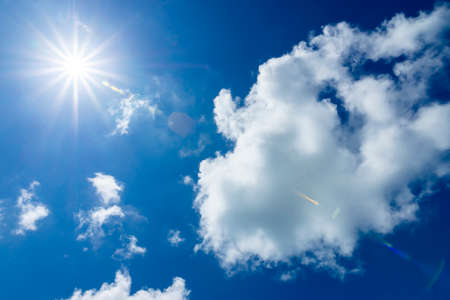 Blue sky with white cloud and sun with flare. Banque d'images