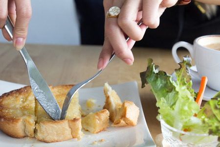 Woman eating Breakfast or coffee break time, toast bread topping with butter, sugar, milk or chocolate, very popular dessert serves with coffee, tea, milk or hot chocolate in coffee shop or restaurant, morning food set.