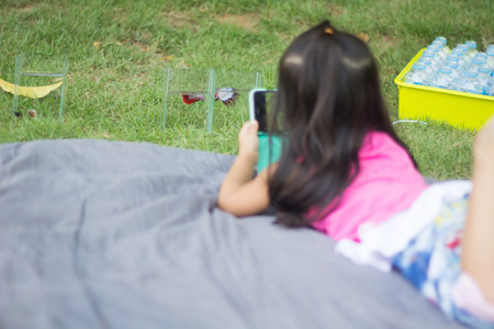 a girl use moblie phone taking photo of betta fish on the grass field ground floor.