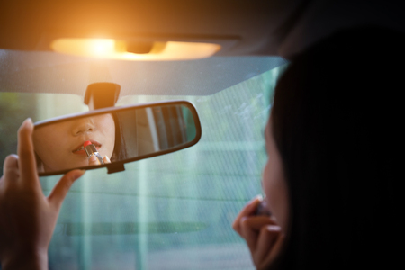 Young woman looking in rear view mirror and putting make up in car. modern busy life. beautiful girl sitting in drivers seat of car doing make up, applying lipstick.