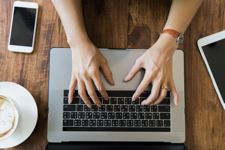 Top view businesswoman hand using laptop on wooden table.young girl working on notebook.female sitting at table with coffee cup browsing internet.smart modern lifestyle. technology concept.