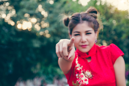 Young Chinese woman dressing traditional costume for Chinese new year festival. girl smile and pointing finger hand at you in chinese temple. Stock Photo