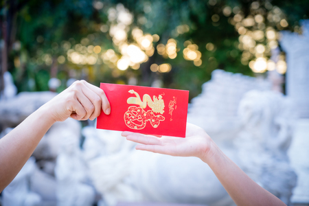 Close up hand holding red letter, sending and receiving red envelope Symbols of the Chinese New Year on golden bokeh background. gifts, festivals and celebration concept.