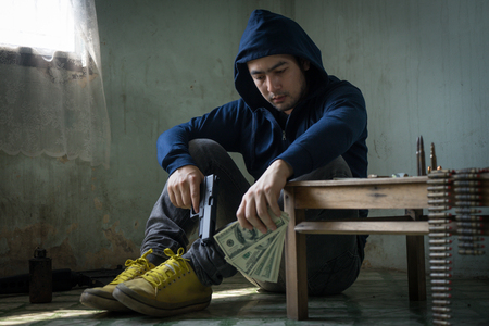 Terrorist sitting in dark and dirty room feeling despair, depressed and sad thinking about bad things. Young hopeless man hands holding gun and money. Drug dealer, criminal with weapons concept. Stock Photo