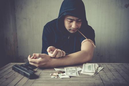 Man using syringe needle, drugs addict. Dangerous guy with gun.