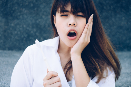 Young woman holding tooth brush hand touching cheek feeling pain. Oral problem. Stock Photo