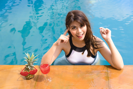 Bikini girl resting in vacation on summer season at swimming pool edge poolside with red wine.Sexy lady relaxing at the pool with cosmopolitan cocktail.Asian female smiling with tropical drinking.Beautiful young woman enjoying with cocktail in resort.