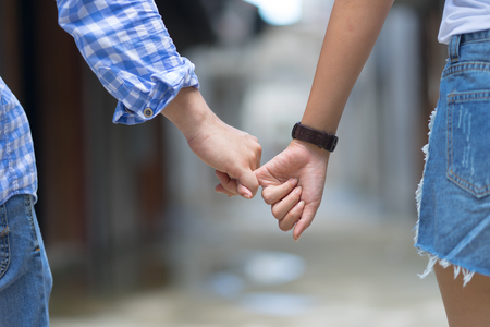 Happy couple holding hands pinky promise or pinky swear.