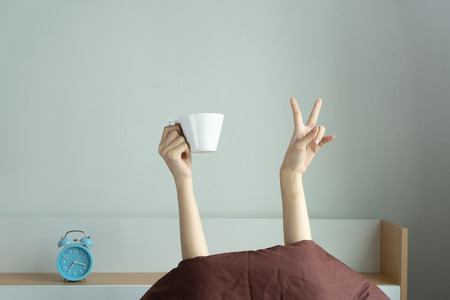 Woman showing the funny victory sign and holding cup behind blanket in the bed room, Young girl with two hands sticking out from the blanket.