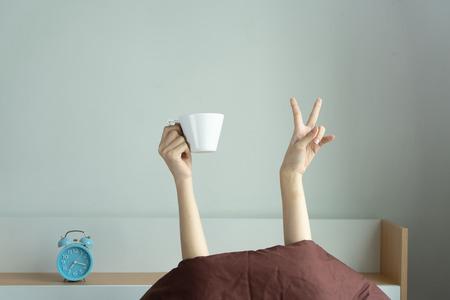 Vrouw toont het grappige overwinningsteken en houdt kopje achter deken in de slaapkamer, jong meisje met twee handen uit de deken steken.
