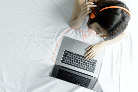 Woman typing laptop on white bed in morning. Young Asian girl using notebook computer listening music at home. Happy female use headphones watching movie on laptop with internet. people technology concept.