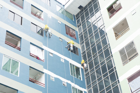 painters hanging on roll, painting color on building wall.