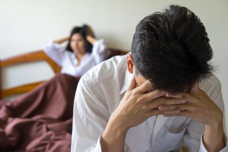Junger besorgter Mann auf dem Bett. Unglückliches Paar, das Probleme im Schlafzimmer hat. Besorgte Frau und Ehemann sorgen sich ernst und verärgert. Familienbeziehungskonflikt, Lebensproblemkonzept.