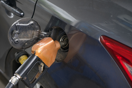 Pumping gasoline fuel in car at gas station pump, refueling Fossil Fuel.