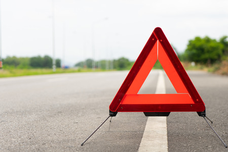 breakdown triangle stands near broken car alongside the road. young man with car broke down on road. Broken car sign on a road concept,