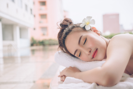 Beautiful Asian woman relaxing with hand massage treatment at beauty spa. Young happy girl in spa salon getting massage. Massage therapy healing medicine and health care concept.