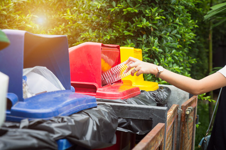 Woman drop plastic bottle into recycle bin.Waste separation trash for different kind of garbage before drop to bin to save the world, environment care.Pollution recycling management concept. Stock fotó